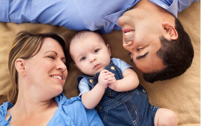 baby-boy-with-parents-at-bed